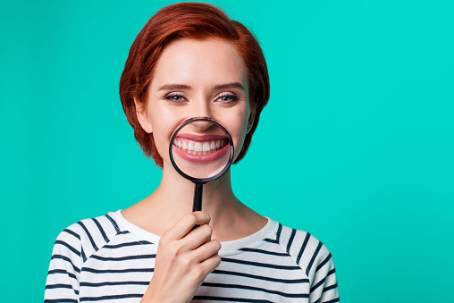 Woman holding magnifying glass over her teeth
